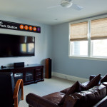Here you can see a spacious media room—note the grouped windows, a classic marker of Cape Cod homes.