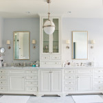 On to the master bath! Note the inset cabinet with elaborate doors and drawers, decorative hardware and lighting, with Carrara marble counters and a frameless glass shower on the left.
