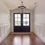 Enter! This stunning entryway has stout mahogany doors, a study in the early American style of housing. Note the painted wood wainscoting, herringbone pattern white oak flooring, and groin vault ceiling.
